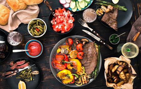 ステーキと野菜のグリル、暗い木製のテーブル、上面にビールやワイン。ディナー テーブルのコンセプト