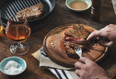 夕食のテーブルのコンセプトです。男は、木製のテーブルで網焼きステーキを食べています。