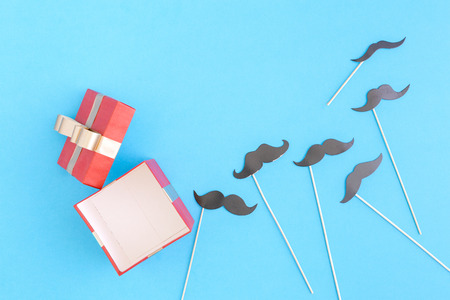 Open red gift box with paper mustaches on blue background.  Fathers Day concept. Flat lay. Top view Stock Photo
