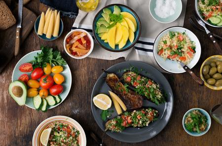 木製のテーブル、トップ ビューで健康的な食品の料理のセットです。ぬいぐるみナス、ブルガー、果物と野菜のサラダ