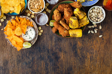 Fried chicken, sauces,  beer, potato chips, nachos, peanuts, pistachios and crackers on a wooden table with border, top view Stockfoto