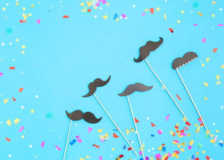 Fathers Day concept. Confetti and paper mustaches on blue background. Flat lay. Top view Stock Photo