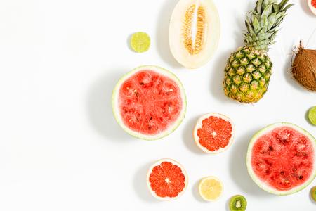 創造的なレイアウトはスイカ、ココナッツ、メロン、グレープ フルーツ、ライム、レモン ボーダーと白い背景から成っています。フラットが横たわ 写真素材