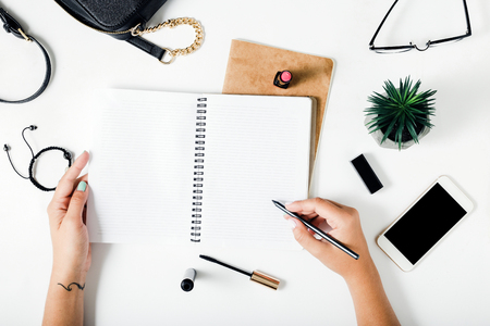 Woman hands writing in a notebook on a white table with female accessories. Concept feminine working place