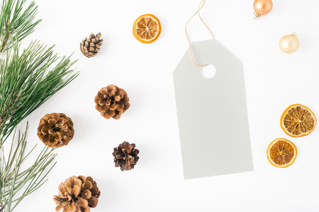Big price tag with fir branch, pine cones, dry orange and Christmas balls on white background, top view. Flat lay composition