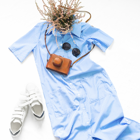 Look female clothes on a white background. Blue striped dress with sunglasses, white sneakers and vintage camera on white background. Beauty blog concept. Flat lay. Top view