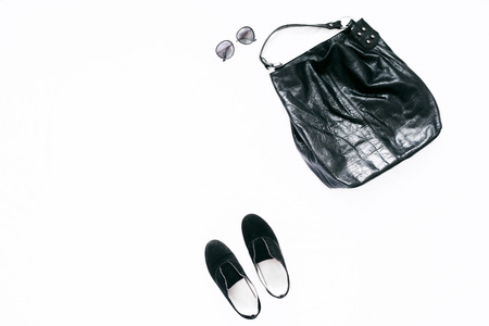 Female leather bag, shoes and sunglasses on white background. Beauty blog concept. Flat lay. Top view