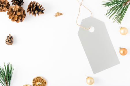 Christmas background with big price tag and decorations on white background, top view. Flat lay