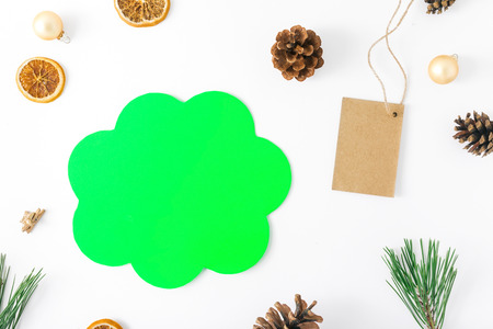 Flat lay christmas background with sign of thought, price tag and decorations on white background, top view