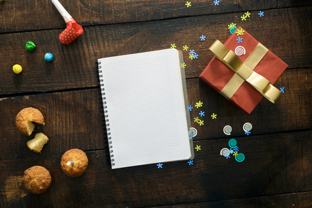 Empty notebook with various party confetti and red gift box on wooden background, top view