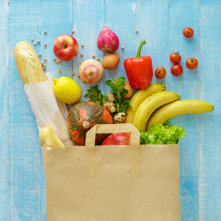 Paper bag of different health food on blue wooden background. Top view. Flat lay Banque d'images