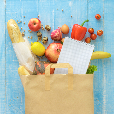 Paper bag of different fresh health food and notebook on blue wooden background. Top view. Flat lay Stock Photo
