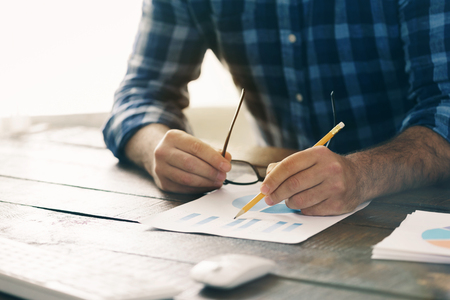 Man analyzes the data and graphs in the home office, front view Stock Photo