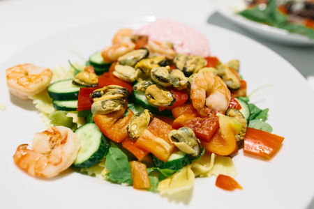 Fresh seafood salad on white plate close up