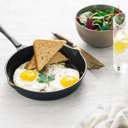 Breakfast table. Fried egg in frying pan on white wooden table with salad and lemon water