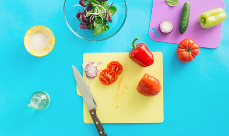 Ingredients for cooking summer salad on blue background, top view. Healthy food background