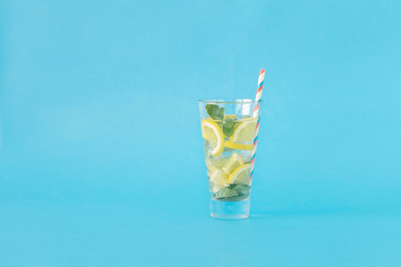 Refreshing summer cocktail with lemon and mint on blue background