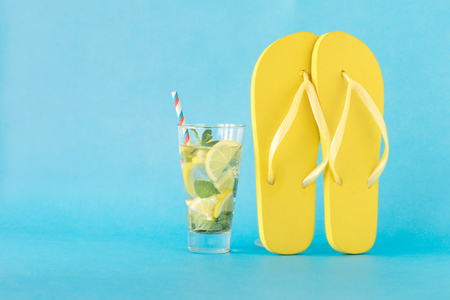 Colorful summer background. Summer refreshing cocktail with flip flops on blue background with copy space