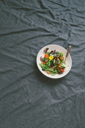 Summer salad with vegetables and flowers nasturtium and violets on bed, top view. Healthy food concept