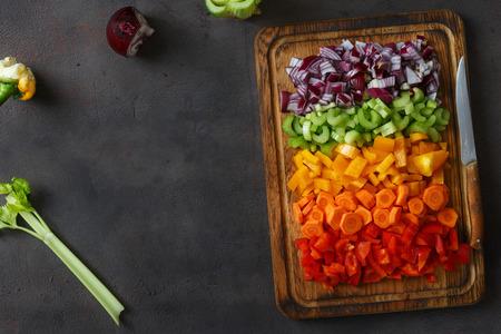 Marco de verduras frescas picadas dispuestas en la tabla de cortar sobre fondo oscuro, vista superior