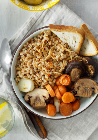 Healthy food concept. Healthy food porridge with baked carrots and mushrooms in bowl on white wooden table, top view 스톡 콘텐츠