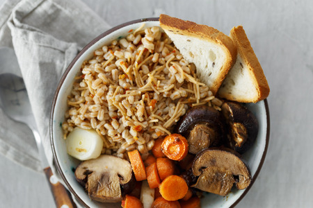 Healthy food concept. Close up healthy food porridge with baked carrots and mushrooms in bowl on white wooden table, top view
