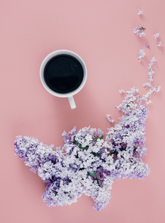 Top view spring minimal concept. Flat lay cup of coffee with branches of lilac flowers on pink background Stock fotó