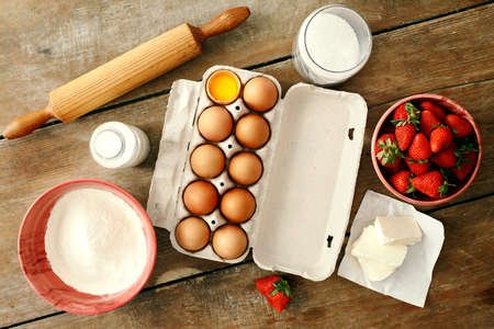 Set raw ingredients for cooking strawberry pie or cake on wooden background. Eggs, flour, milk, sugar, strawberry, top view. Bakery background. Recipe for strawberry pie Imagens
