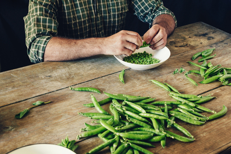 Male hands clean green peas sitting at wooden table in the kitchen. Rustic style. Green peas in bowl on wooden table