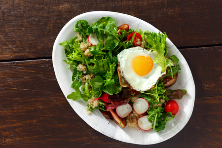 Plate fresh salad with quinoa and fried egg on wooden table. Healthy food clean eating