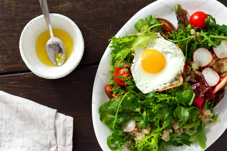 Plate fresh salad with white quinoa, fried egg and sauce on wooden table. Healthy food clean eating