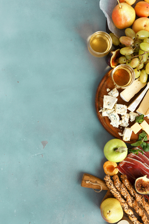 Set wine snacks with glass white wine: grapes, peach, apricot, pear, apples, jamon, hard cheese, brie cheese and roquefort cheese on blue stone background with copy space top view flat lay