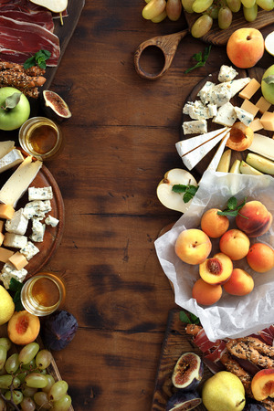 Frame of various wine snacks: grapes, peach, apricot, pear, apples, jamon, hard cheese, brie cheese and roquefort cheese on wooden table top view. Flat lay appetizers table for wine. 写真素材