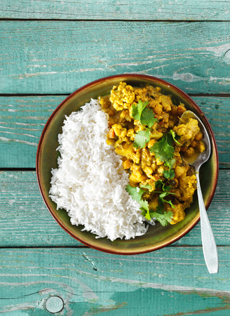 Cauliflower spicy curry with rice on green wooden background copy space top view