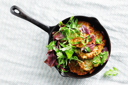 Vegetarian snacks, appetizers courgettes fritters served in pan. Delicious and healthy breakfast on white background, top view Stock Photo