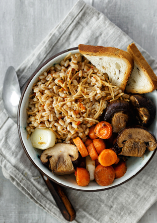 Healthy food porridge with baked carrots and mushrooms in bowl on white wooden table, top view. Healthy food concept