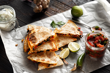 Vegetarian snacks: quesadilla with vegetables and cheese on dark wooden table