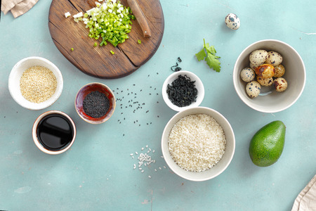 Various raw ingredients for cooking vegetarian poke bowl with quail eggs on blue stone kitchen table top view