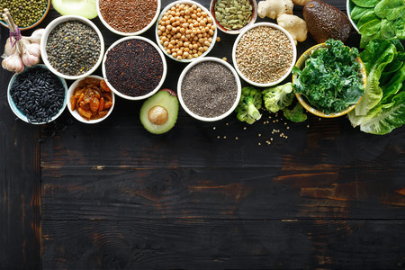 Set superfoods on dark wooden table with copy space. Leaves, cereals and seeds top view. Healthy vegetarian food Banque d'images