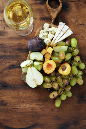 Appetizers table and wine. Fruit and cheese on wooden board. Wine appetizers Reklamní fotografie
