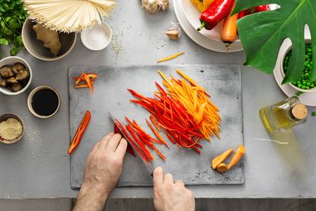Male hand preparing vegetarian thai noodles in home kitchen top view