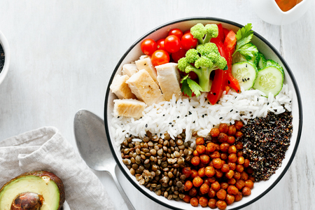 Quinoa, lentil and chickpeas vegetable vegetarian buddha bowl on white wooden table top view. Healthy food Foto de archivo