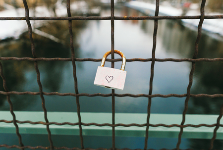 Love forever concept. Padlock with painted heart hanging on the bridge