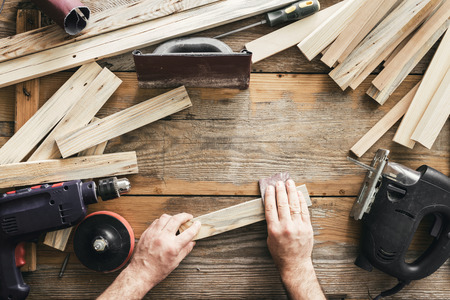 Carpenter working in carpentry workshop. Man sanding manually plank top view Stock Photo