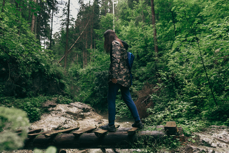 Healthy lifestyle concept. Woman tourist with backpacks walking along forest hiking trail