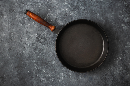Empty round pan with wooden handle on dark stone background top view Фото со стока