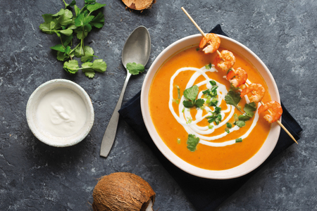 Sweet potato soup with shrimps in bowl top view