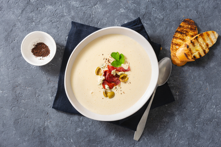 Bowl of cheese soup with bacon and olives top view Stock Photo