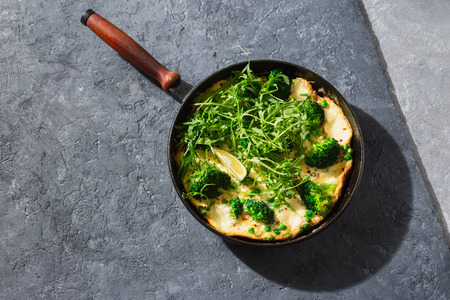 Frittata with broccoli, green peas and mozzarella cheese in frying pan on dark  top view