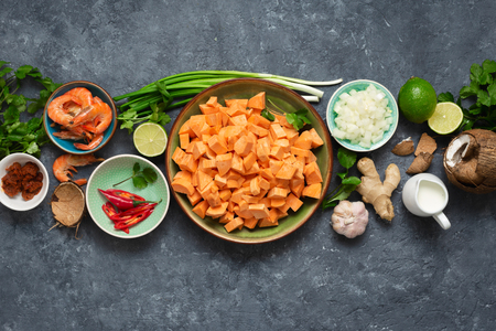 Raw ingredients for cooking sweet potato soup with shrimps on dark  top view